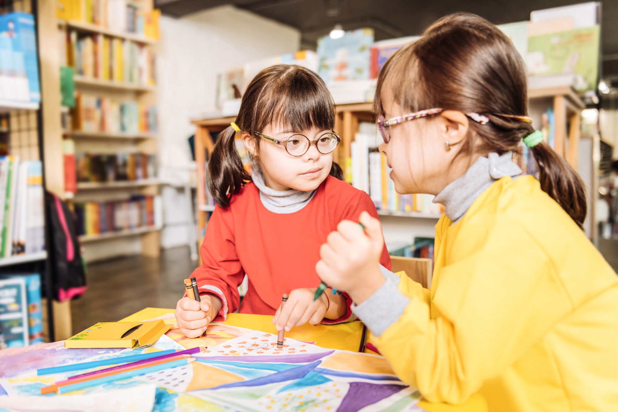 two girls with down syndrome drawing with glasses on