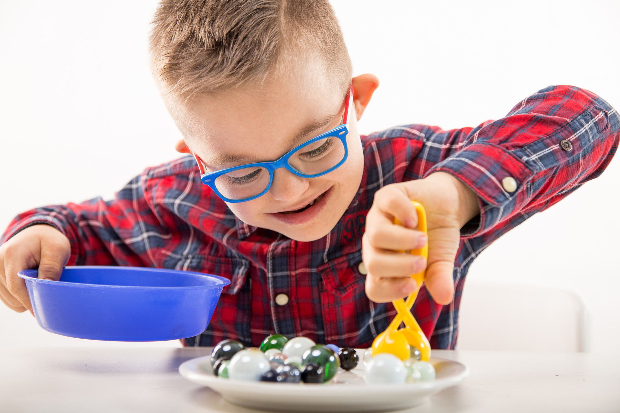 boy with down syndrome picking up marbles from plate
